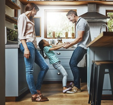 Parents dancing with daughter in new kitchen